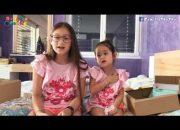 Hai chị em đi học ngoan nên được ba mẹ tặng quà.